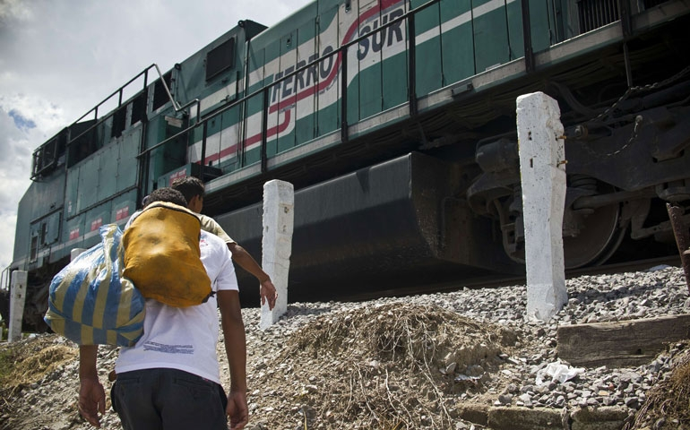 """In Mexico July 22, a Central American migrant walks toward """"La Bestia,"""" a cargo train headed for the U.S. border. (Newscom/AFP/Getty Images/Ronaldo Schemidt)"""