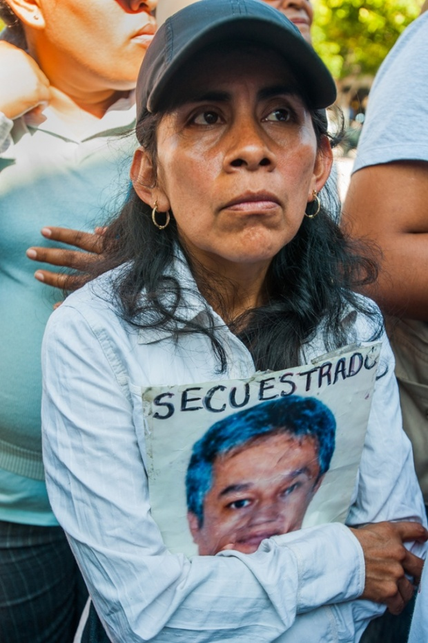 An unidentified woman carries a picture of a family member with the word 'Kidnapped' in Spanish. Photograph: Keith Dannemiller/for the Guardian